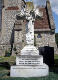 A headstone with angels on a cross